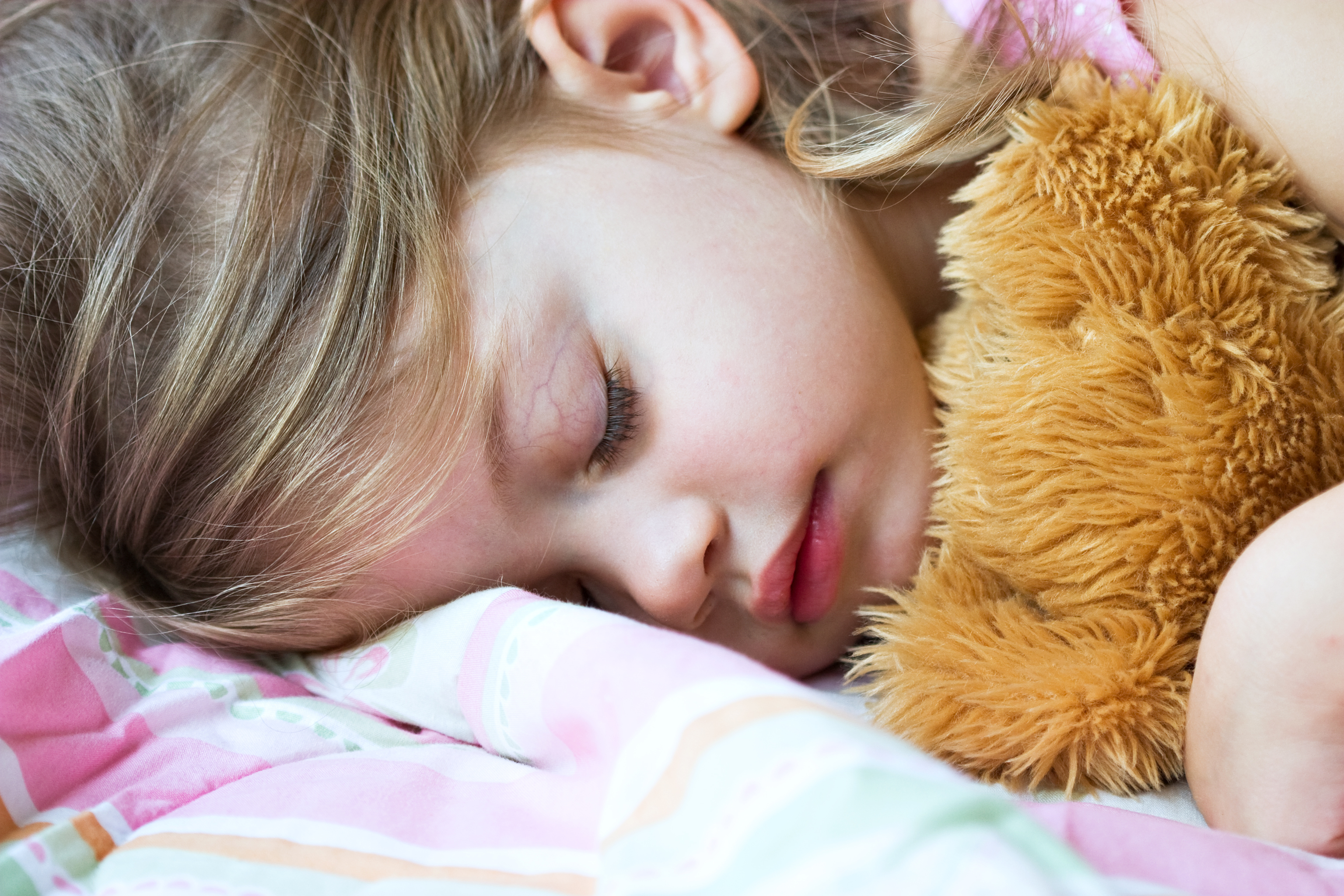 Toddler sleeping with her teddy bear on a pink blanket